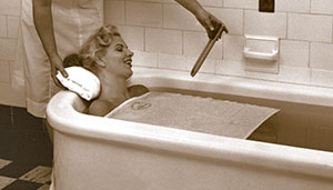 Nostalgic photo of woman relaxing in a tub.