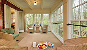 Glass enclosed porch with fresh fruit and coffee awaiting guests.