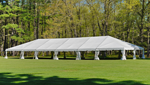 A wedding tent pitched on a lush green field.