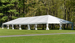 Wedding tent pitched on a lush green field.