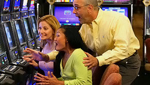 Friends cheer a woman on as she wins on a slot machine.