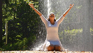 Woman celebrating yoga with a geyser as a backdrop.